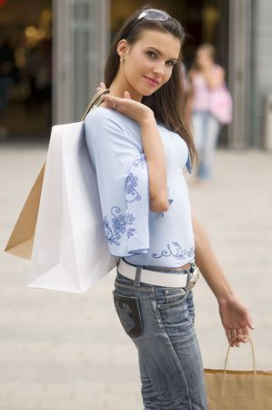 beautiful brunette standing in front of a shop with bags and sun glasses Stock Photo - 3257970