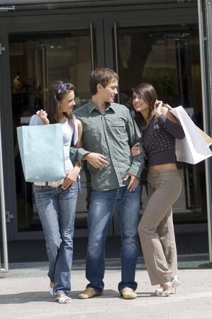 begs: a group of young people just outside of a commercial center with shopping begs Stock Photo