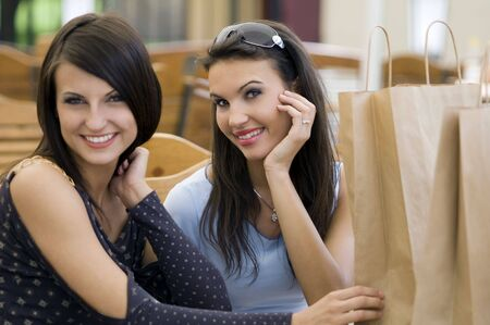 two girls sitting with shopping begs near focus on the right girl Stock Photo