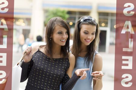 two girls looking at a shop window during sales with a lot of interest Stock Photo - 3257969