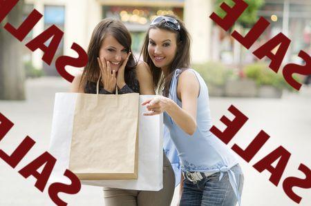 euforia: dos chicas buscan en un escaparate de venta con un mont�n de inter�s
