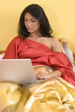 negligee: sensual brunette working with notebook on her bed wearing a red negligee LANG_EVOIMAGES