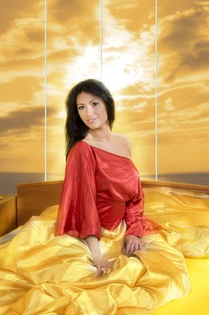 sensual brunette with red nightgown posing in bed between the sheet Stock Photo - 3307871