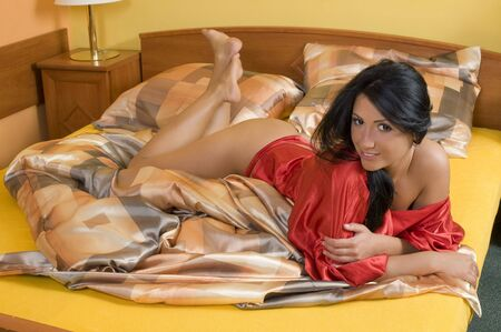 sensual brunette with red nightgown laying down in a bed with yellow sheet Stock Photo - 3307908