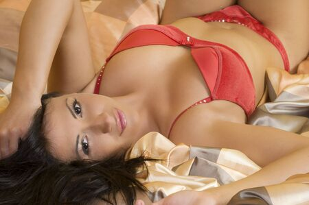 close up of a cute brunette laying down and wearing red lingerie Stock Photo - 3307896