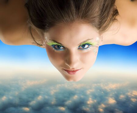 cute brunette with green eyelashes flying as a bird over the clouds Stock Photo - 3348489