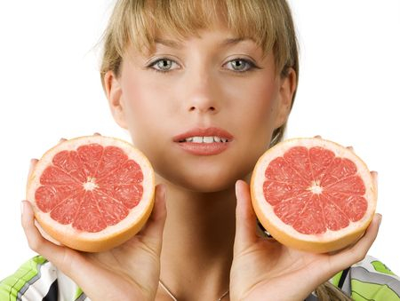 close up of blond girl with two half grapefruit in her hands photo