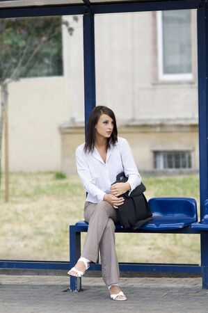 woman sitting down at the bus stop waiting Stock Photo