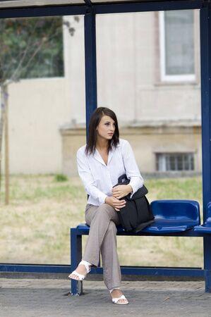 bus stop: mujer de negocios sentado en la parada del autob�s de espera  Foto de archivo