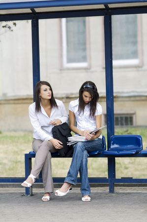 fermata bus: due giovani cute e bruna in attesa di un autobus alla fermata