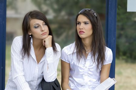 bus stop: close up of two nice brunette sitting down outdoor at the bus stop