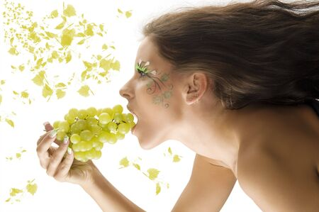 pretty girl with windly hair eating grape with a nice body paint on her face Stock Photo - 3465333