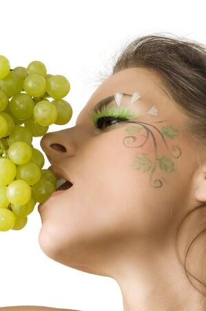 nice and sexy girl with a nice paint on her face in act to eat some green grape Stock Photo - 3465326