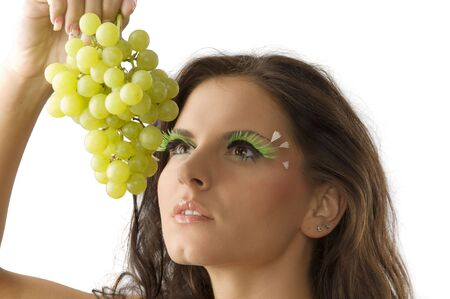 portrait of a young and sensual brunette with a green grape photo