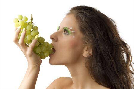 pretty brunette eating green grape and having green eyelashes photo