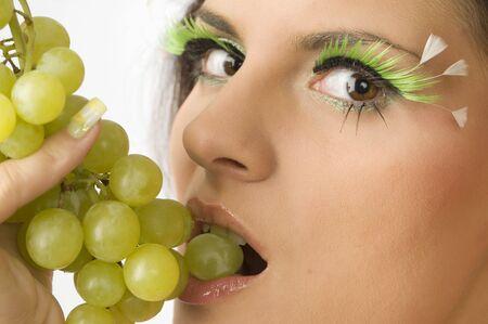 close up of a sensual girl with green eyelashes and grape between lips photo