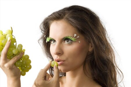 cute brunette with green artificial eyelashes eating a green grape Stock Photo - 3468103