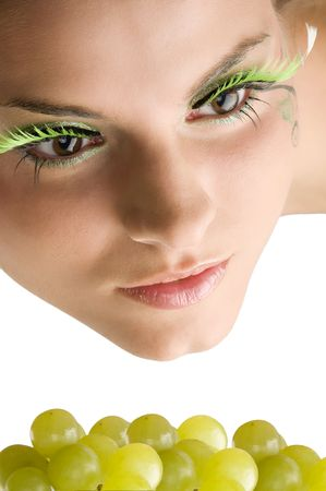 close up of a cute girl with artificial eyelashes and some green grape photo