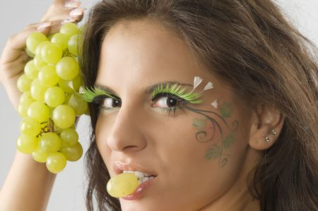 nice girl with a grape between the lips and her face painted with leaf photo