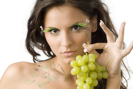pretty and sensual girl with bodypaint and eyelashes showing grape with hand Stock Photo - 3468107