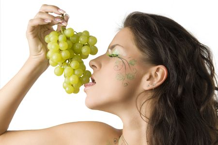 sensual brunette with leaf painted on face licking green grape Stock Photo - 3468102