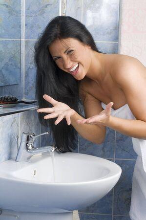 daily routine: bonita chica con el pelo negro jugando con el agua durante su rutina diaria