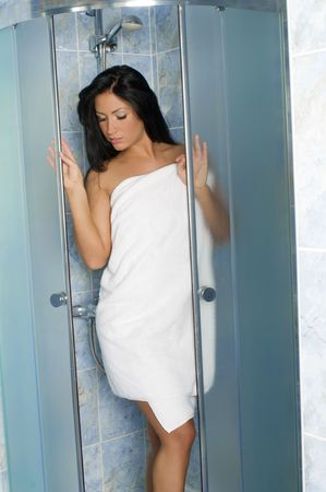 pretty girl with white towel inside a shower box in a bathroom