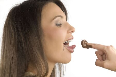 nice closeup of a brunette licking some chocolate cream from her finger photo