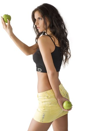 cute young brunette looking at a green apple with big interest photo