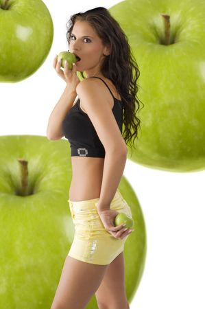 cute brunette with yellow mini skirt biting a green apple photo