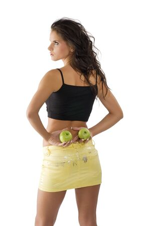 cute young woman with yellow mini skirt and green apple in her hand photo