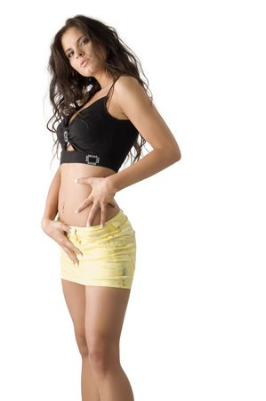 mini skirt: sensual brunette with short yellow skirt and a black top taking pose