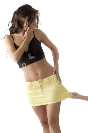 cute brunette with her yellow skirt pulled from a hand looking surprise