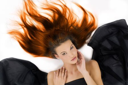 sensual girl laying down with hair in flame on floor and black fabric around Stock Photo - 3558134