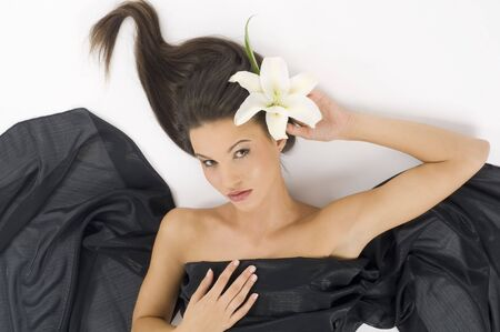 carnal: sweet young and cute brunette laying down with a white lily and waved hair LANG_EVOIMAGES