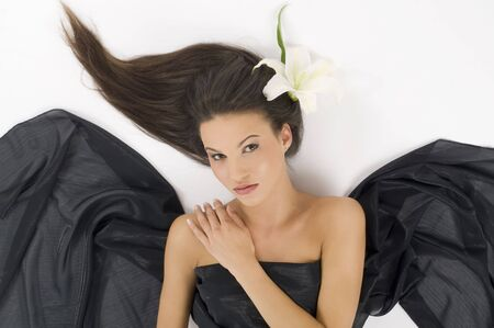 carnal: sweet portrait of a young and cute brunette laying down with a white lily in hair