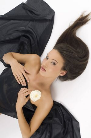 carnal: young and sweet brunette laying down with hair waved and a white rose LANG_EVOIMAGES