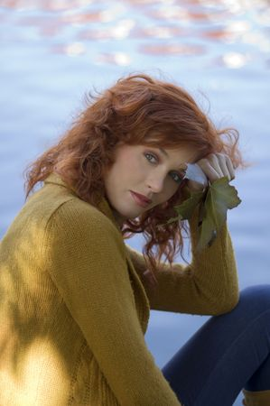 romantic autumn portrait of a red haired woman near a river photo