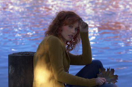 red haired woman with yellow cardigan and blue river water in background photo