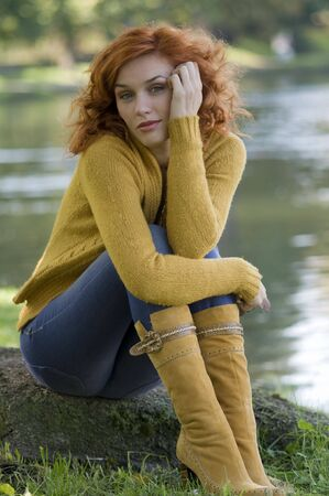 red jeans: pretty and young woman posing near a river in fall season LANG_EVOIMAGES