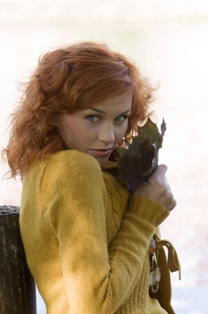 pretty close up of red-haired woman playing with leaf outdoor photo