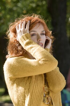 fashion portrait of young red woman in yellow autumn clothes photo