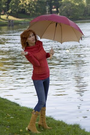beautiful woman with umbrella looking up the sky if stop raining photo