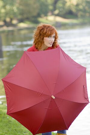 Pretty red haired girl near river playing behind a red umbrella photo