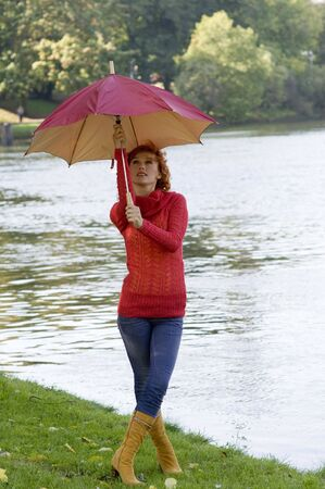 very nice girl closing her umbrella in park near a river photo