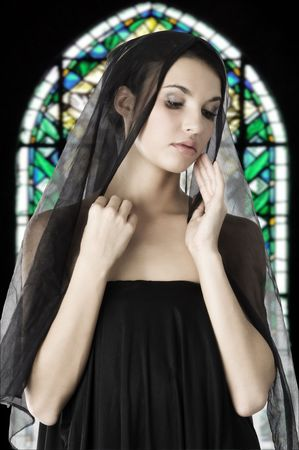 beautiful woman with a black veil on her head in a church like a madonna photo