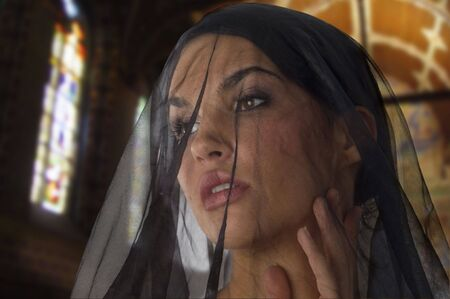 cute woman like widow with a black transparent veil on her face in church photo