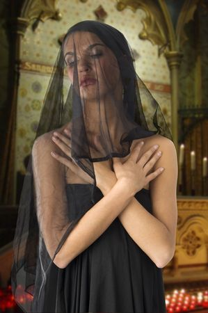 vestal: very cute widow in black dress and veil on face inside a church