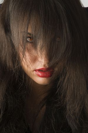 woman with black hair on face and red eyes looking anger in camera photo