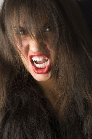 close up of brunette with teeth like a vampire and red eyes photo